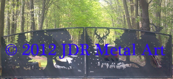Rustic automatic driveway gates featuring cutouts of deer fox and trees plasma cut by JDR Metal Art.