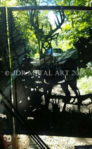 Picture of ornamental deer style driveway gate taken from inside skid steer..