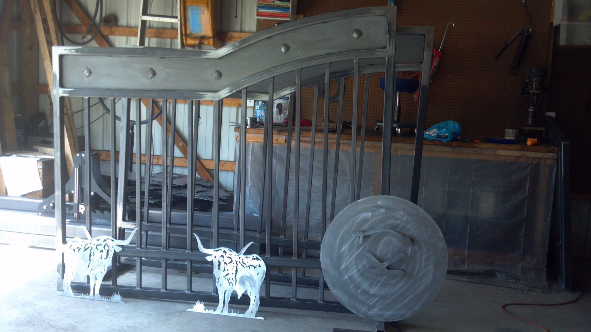 Picture of custom gate with arched top and sheet metal adorned with clavos and a ranch brand silhouette.