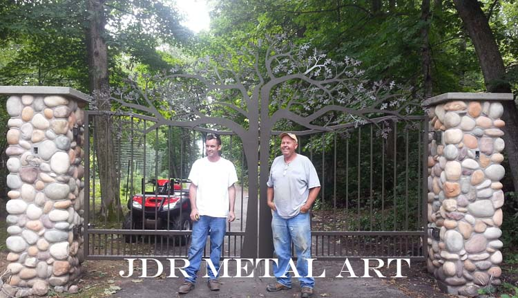 Custom driveway gates with tree design plasma cut by jdr metal art. They are mounted to stone columns and have a plasma cut metal art tree design.