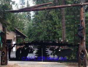 Ornamental driveway gates in front of Washington home. Bear and moose silhouettes plasma cut by JDR Metal Art.