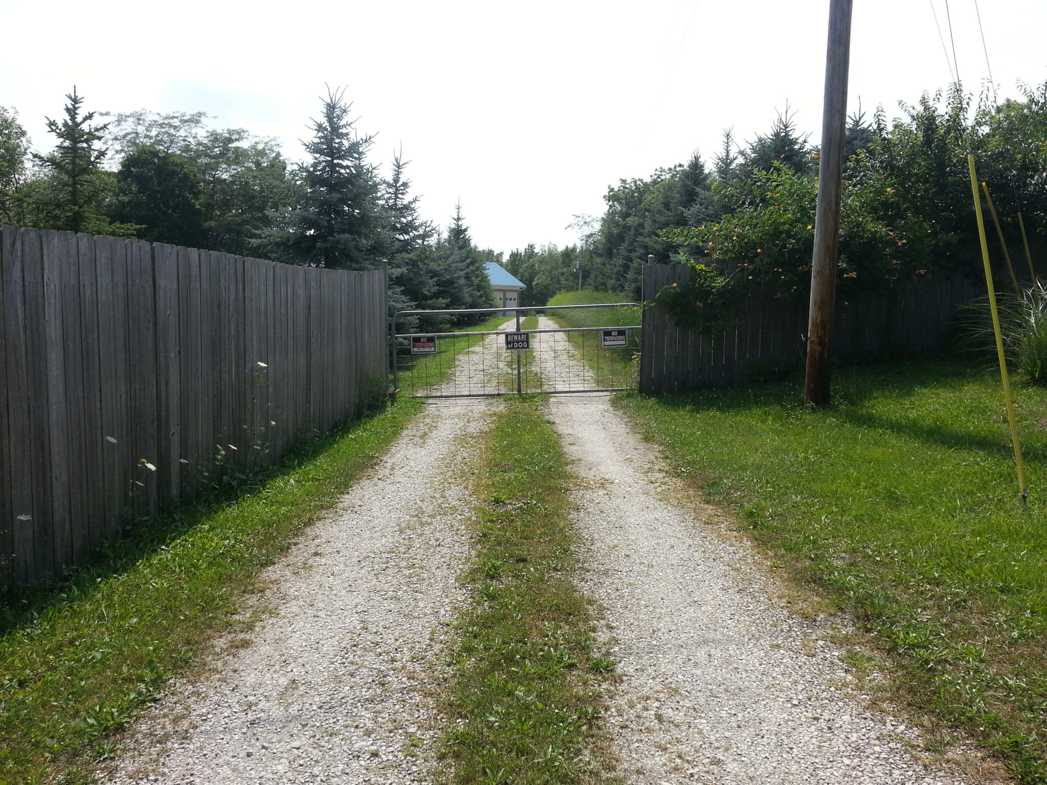 Original driveway entrance before we updated it by installing custom sliding driveway gates.