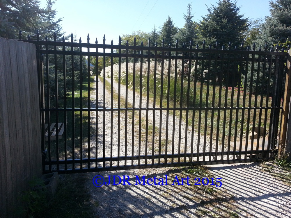 Custom sliding driveway gates with pickets and spears by JDR Metal Art.
