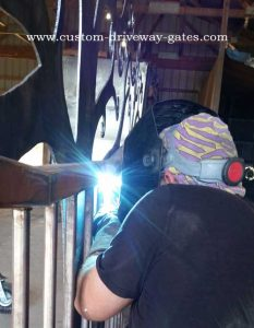 Welding on plasma cut tree silhouette to driveway gate.