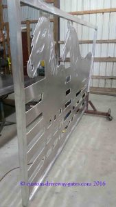 Shiny aluminum driveway gates with horse designs which have been plasma cut by JDR Metal Art.