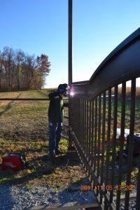 Welding decorative ranch gate onto gate post.