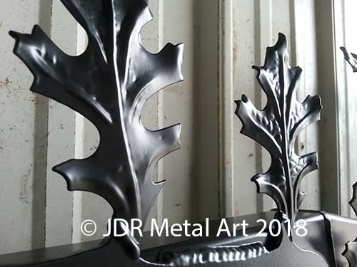 Stamped leaves welded on tree gate