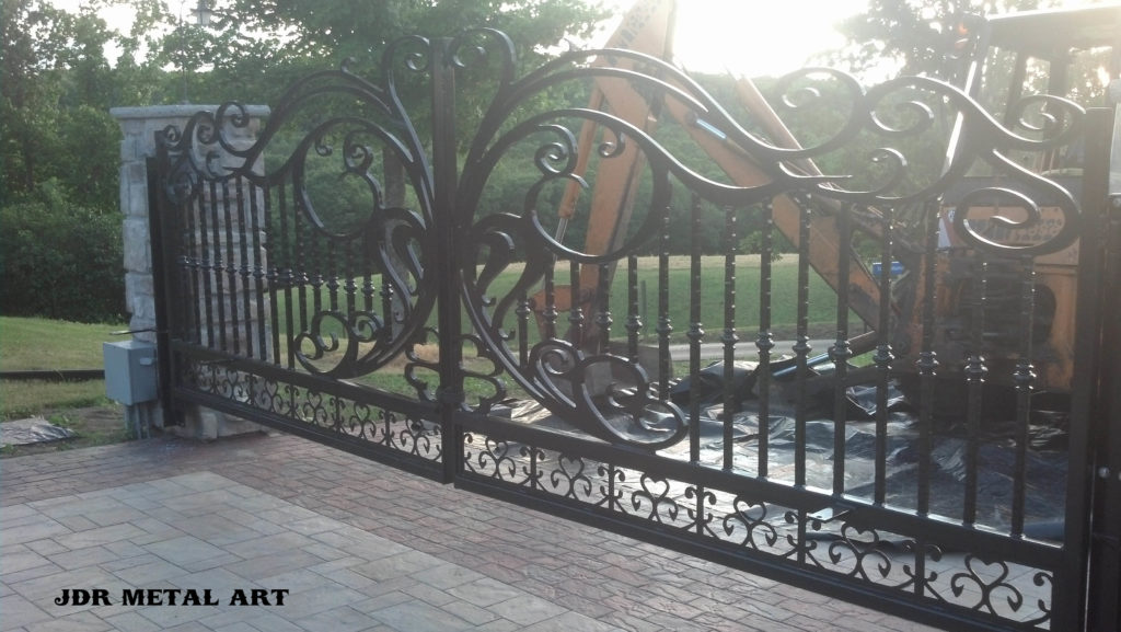 Wrought Iron driveway gate by JDR Metal Art, hung from masonry columns.