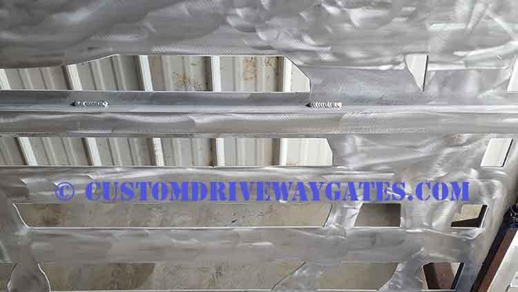 Automatic aluminum gate operator mounting bracket on back of custom gate