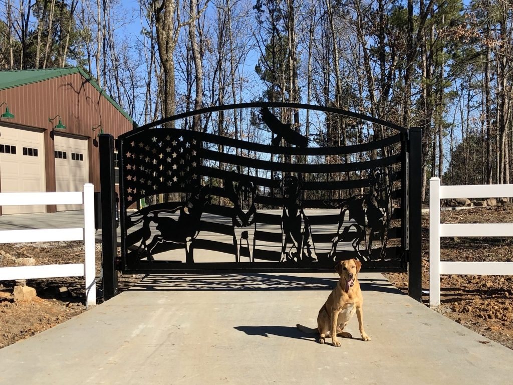 American flag themed driveway gate with dogs