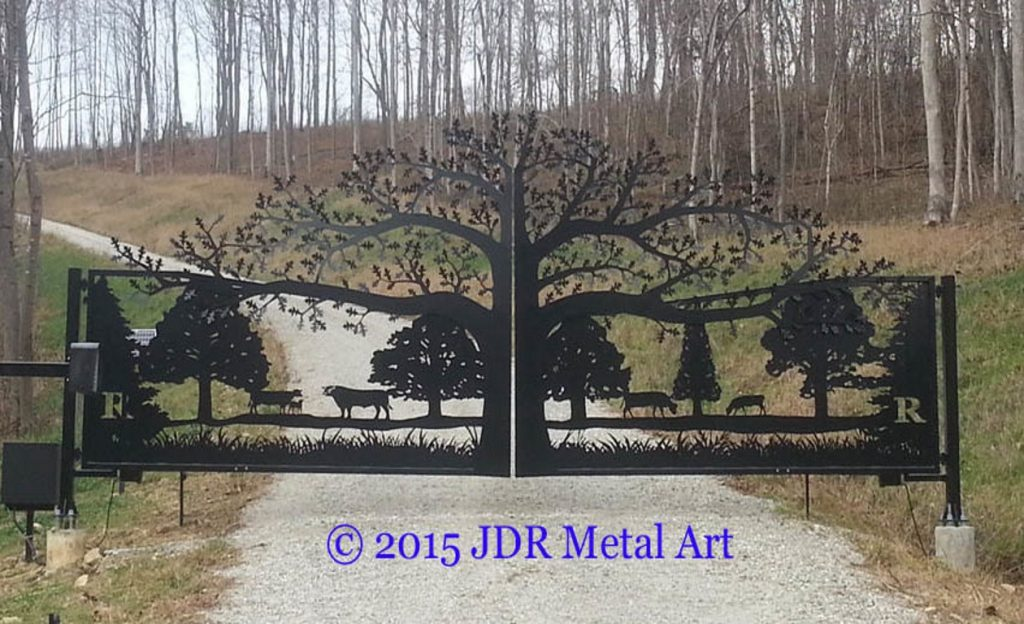 Tree of Life Driveway Gate at ornamental entrance to fenced property with gravel driveway.
