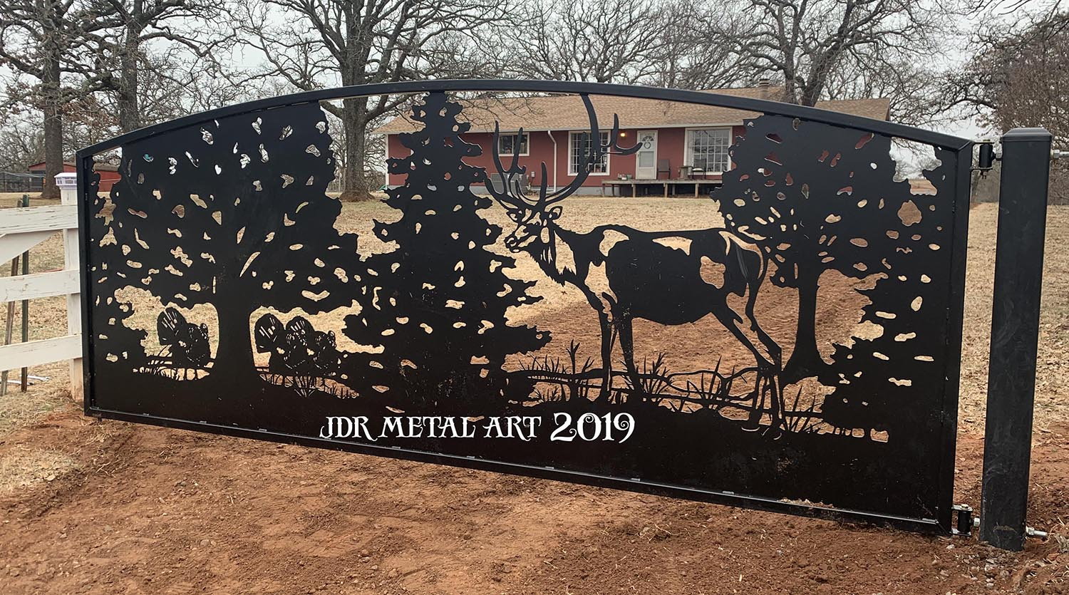 Elk and turkey design on metal farm gate in Oklahoma.