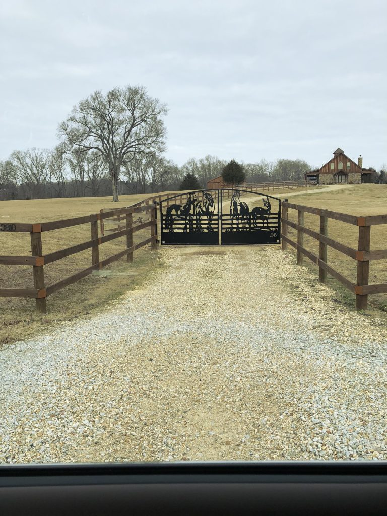 Custom farm gates at a farm driveway entrance.