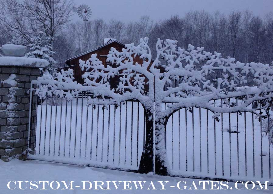 Metal art driveway gate covered in snow with barn in the background.