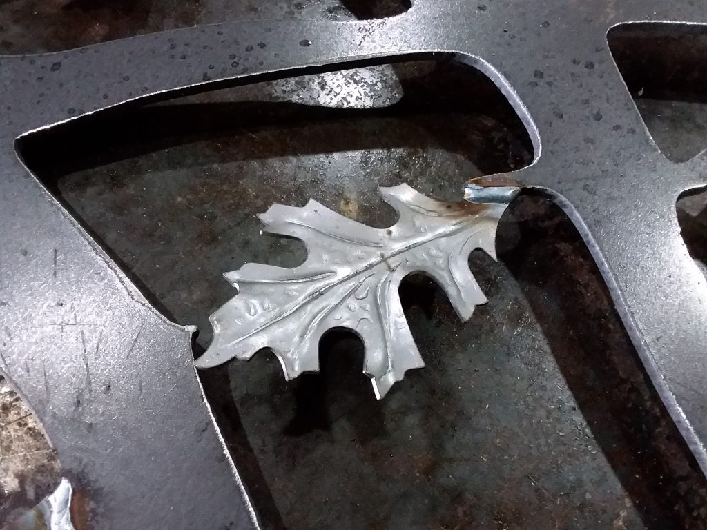 Iron leaf that has been welded onto the iron driveway gate.