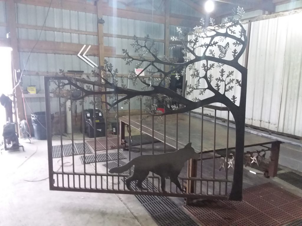 Photo of German shepherd and butterfly emblem on ornamental gate.