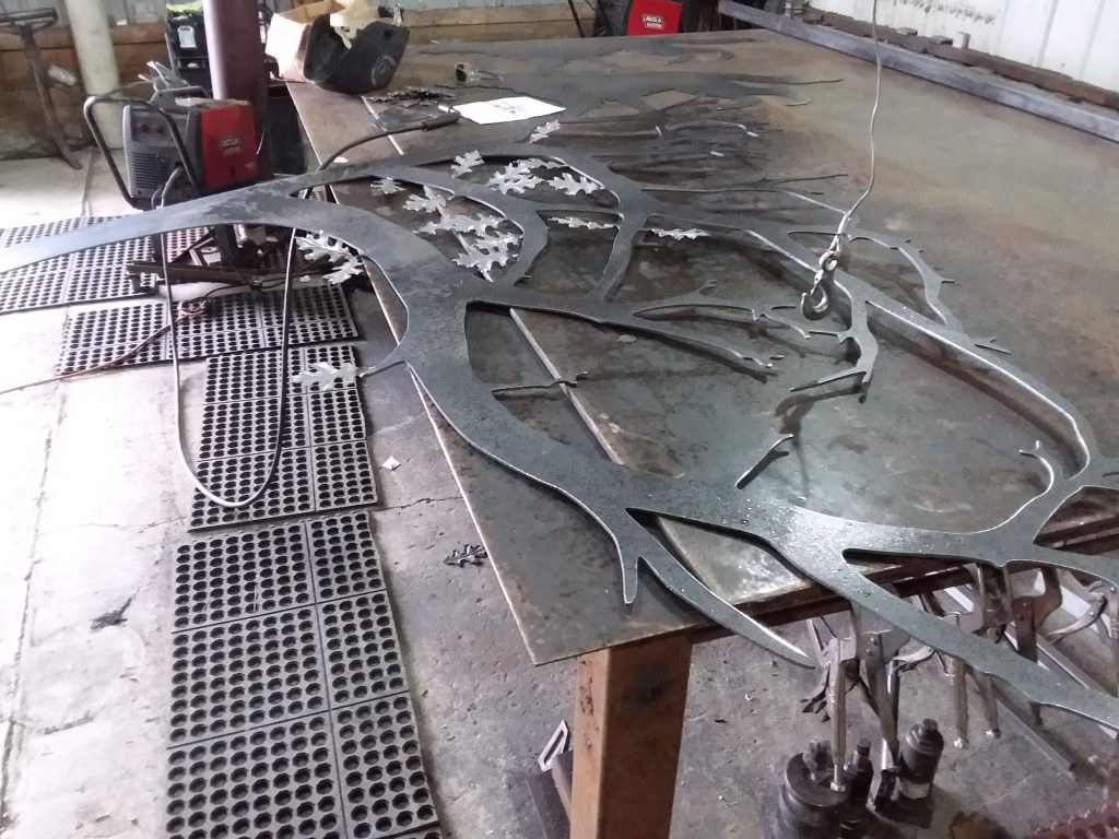 Custom builder of driveway gate with photo of progress welding leaves.
