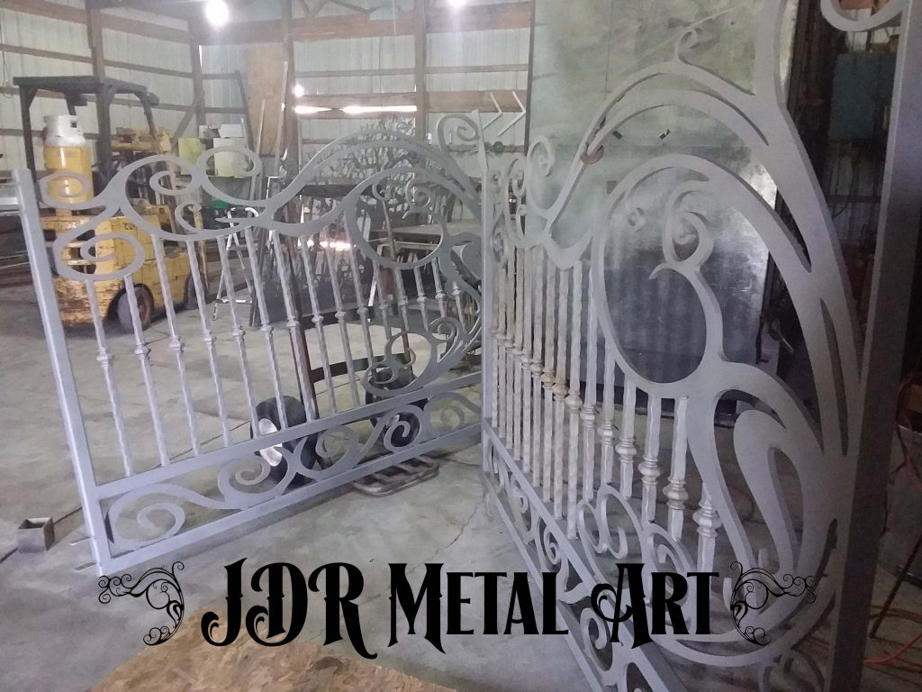 A set of custom dual swing steel driveway gates after they were sandblasted.
