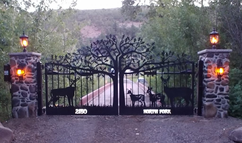 A photo of customized driveway gate with tree and deer theme.