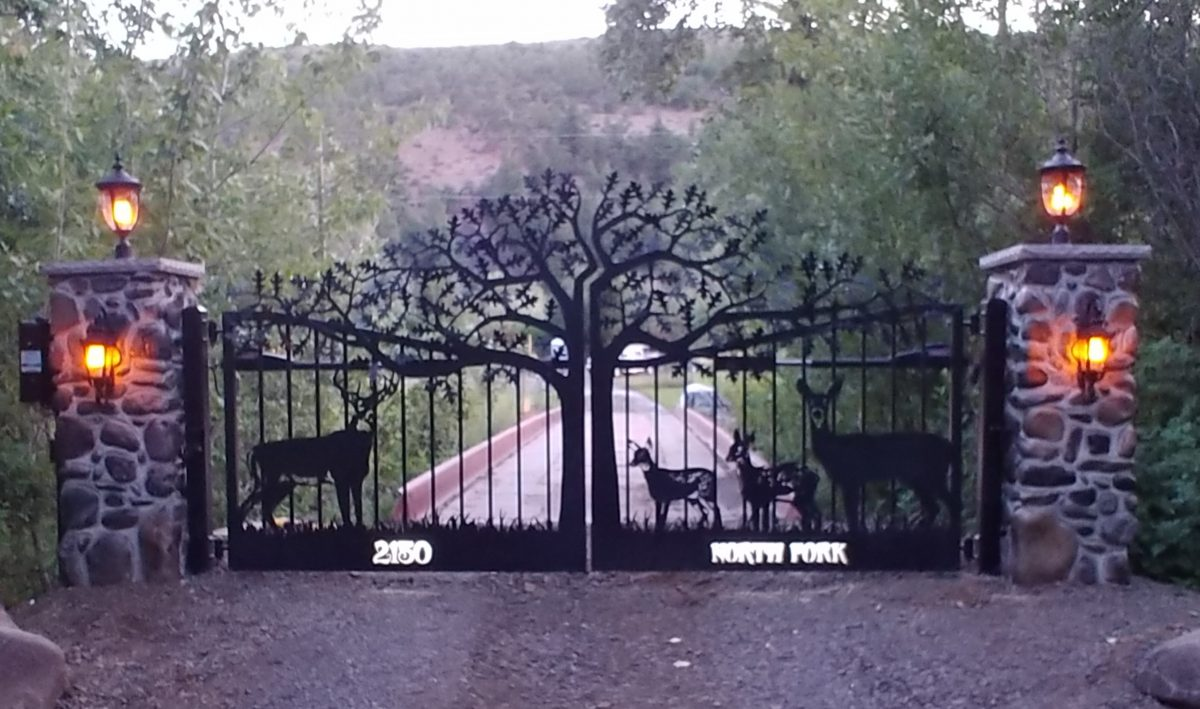 A driveway gate with customized driveway gates with tree and deer theme.