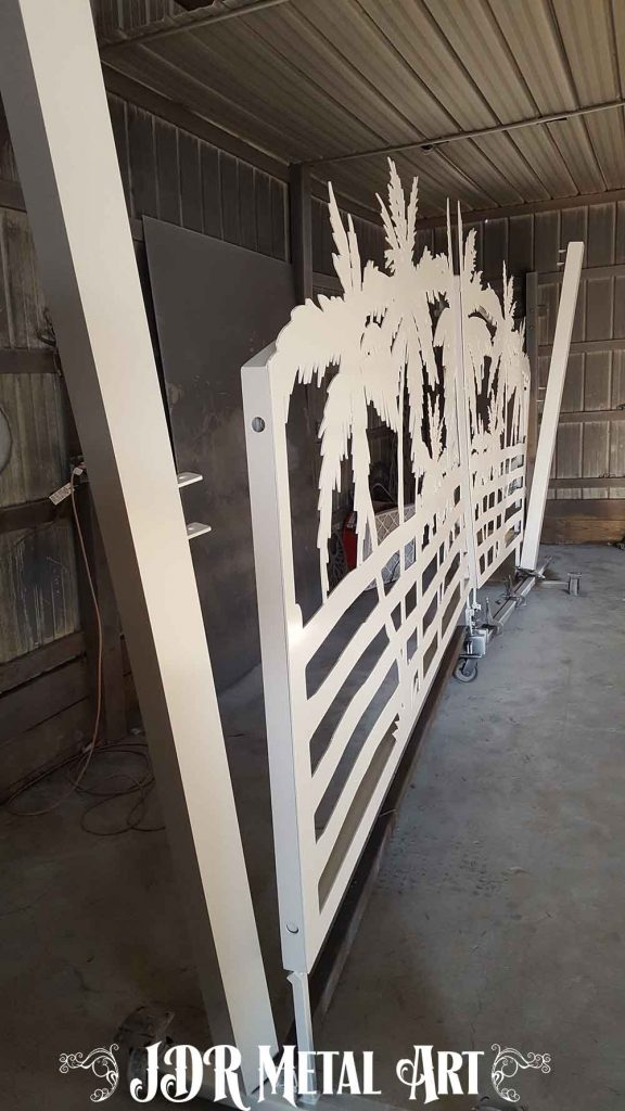 Side view of white powder coated aluminum drive gates and gate posts.