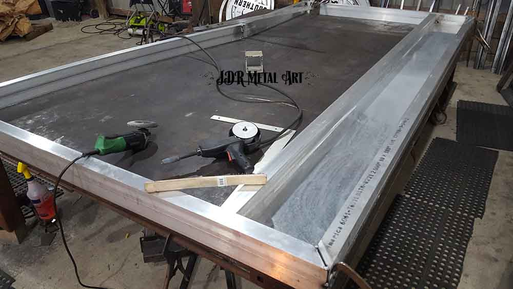 Assembling aluminum sheet and square tubing.