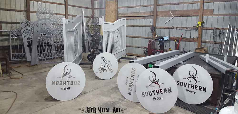 Aluminum gates and signs that have been sandblasted in preparation for powder coating.