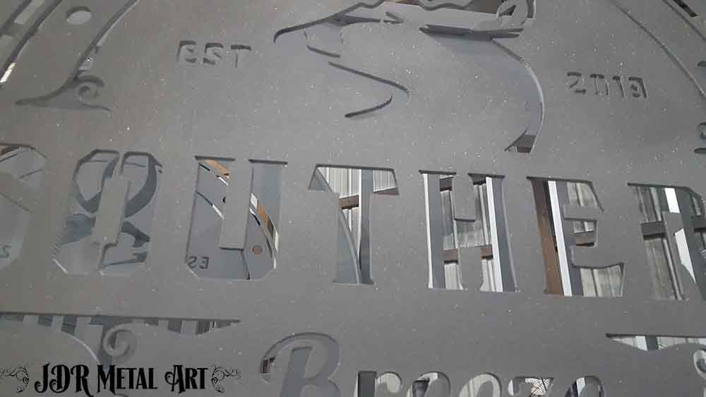 Sandblasted metal logo for custom Pensacola driveway gate made from aluminum.
