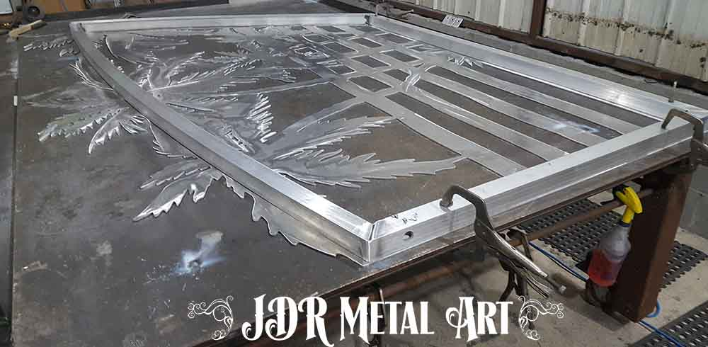 Aluminum gate panel laying on welding table.