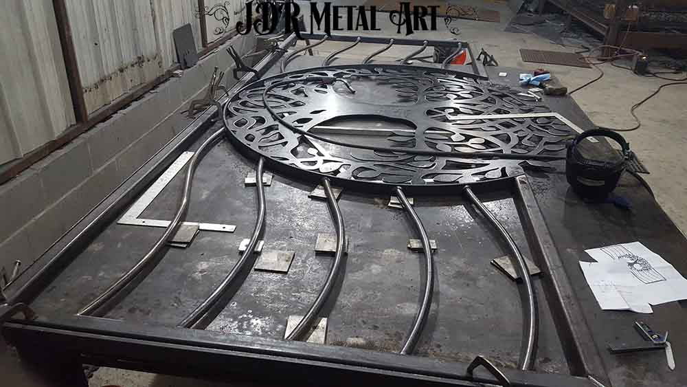 Fabrication of tree of life driveway gate on welding table.