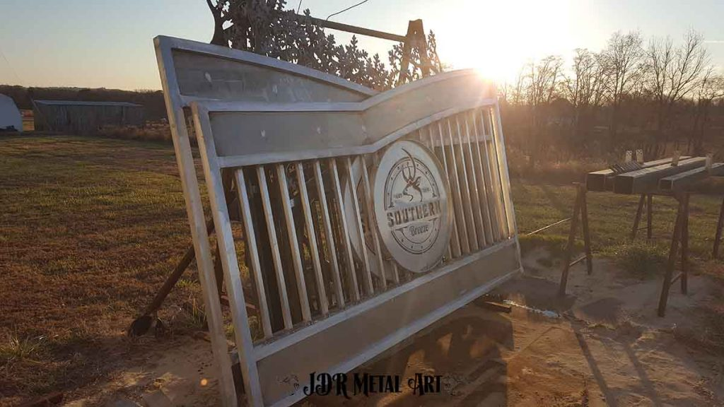 Sunrise over aluminum driveway gates racked up to be sandblasted.