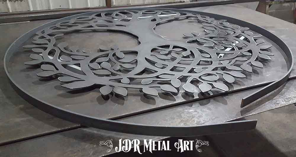 "Rolled flat bar and design of tree cut out of 1/4"" plate steel."