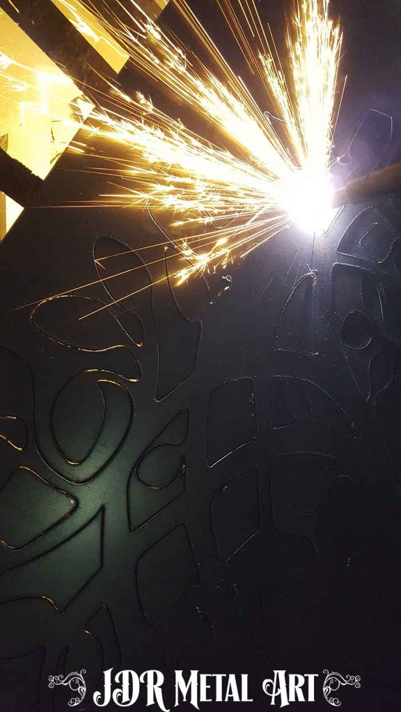 Plasma cutting the metal art tree of life from steel plate.