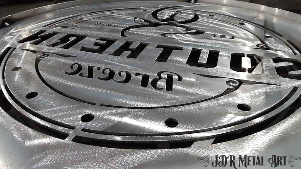 Polished aluminum sheet metal with plasma cut gate logo.