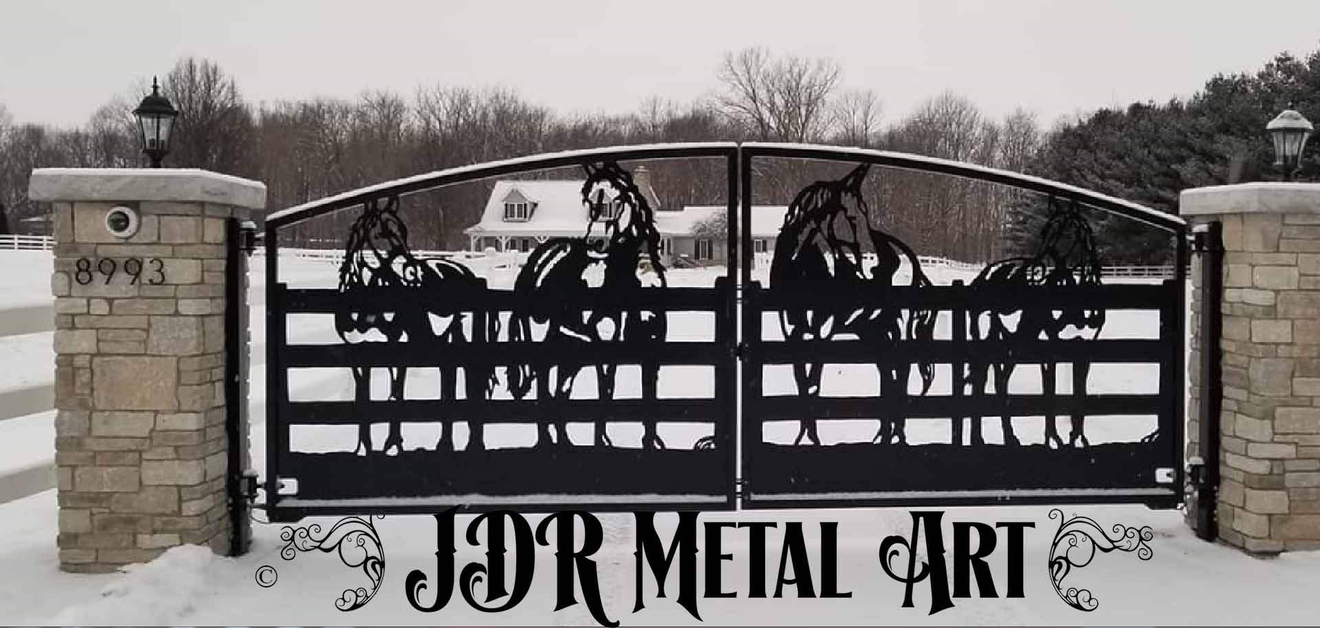 Horse farm driveway gates with silhouettes of four horses at a wooden fence.