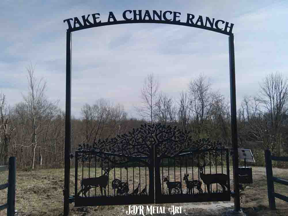 Metal art driveway gates for ranch entrance.