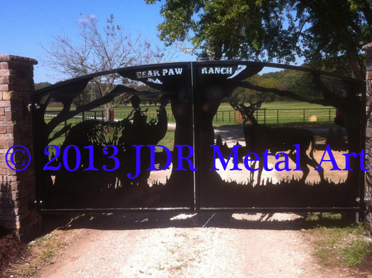 Best driveway gates in the United States, with bear and deer design, each flanking a large tree in the center with mountains in the background.