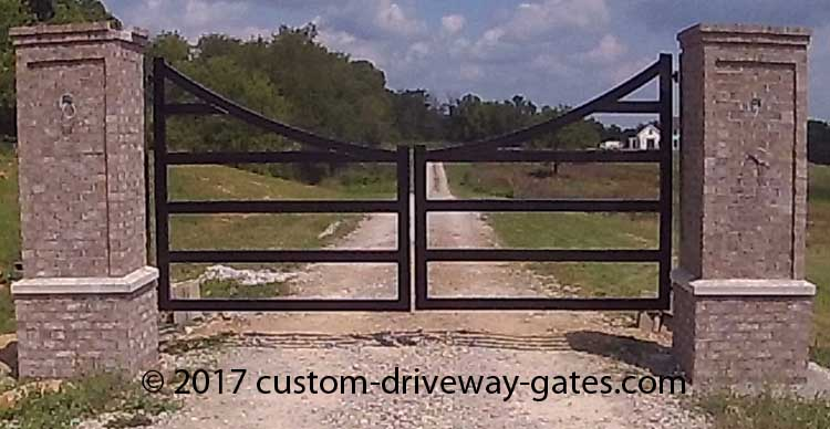 Swinging driveway gates hanging from columns with black powder coat and hinges.