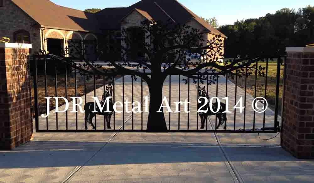 Black single swing driveway gates hanging from brick columns.