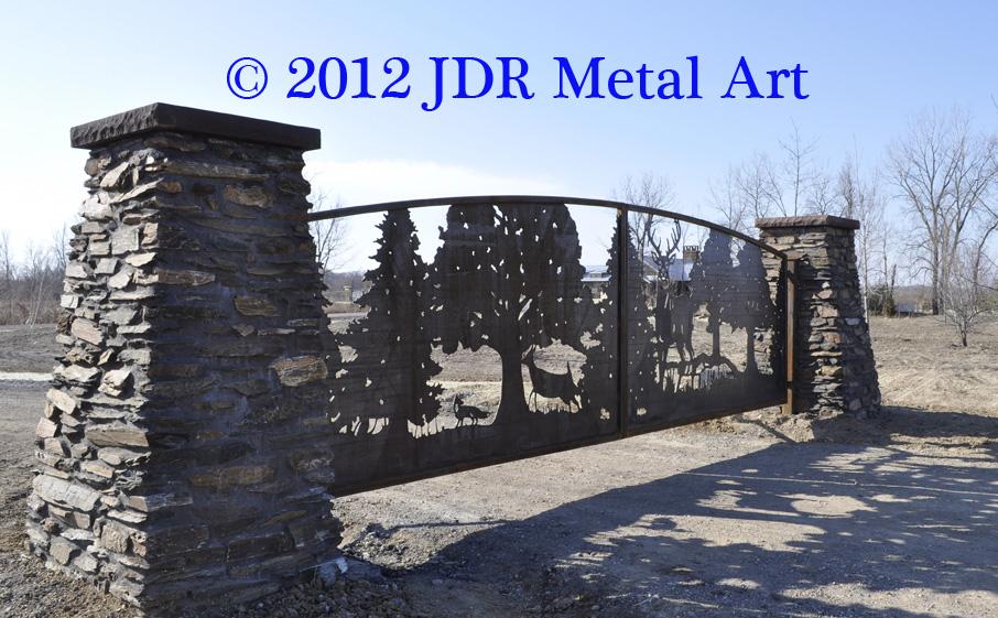 Corten steel metal driveway gate hanging from rock columns.