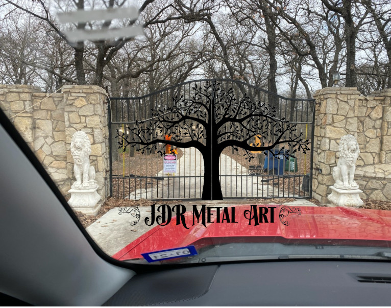 Metal driveway gates with large ornate oak tree hanging from stone columns.