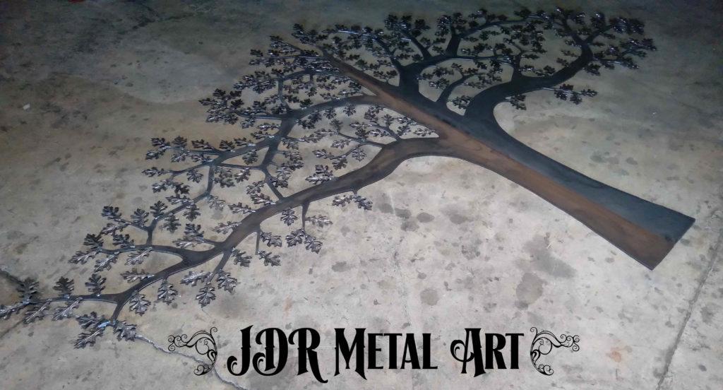 Plasma cut metal tree with oak leaves on concrete floor.